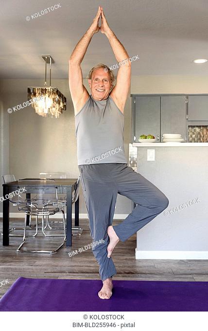 Caucasian man practicing yoga in home