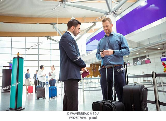 Business people waiting at check-in counter with luggage