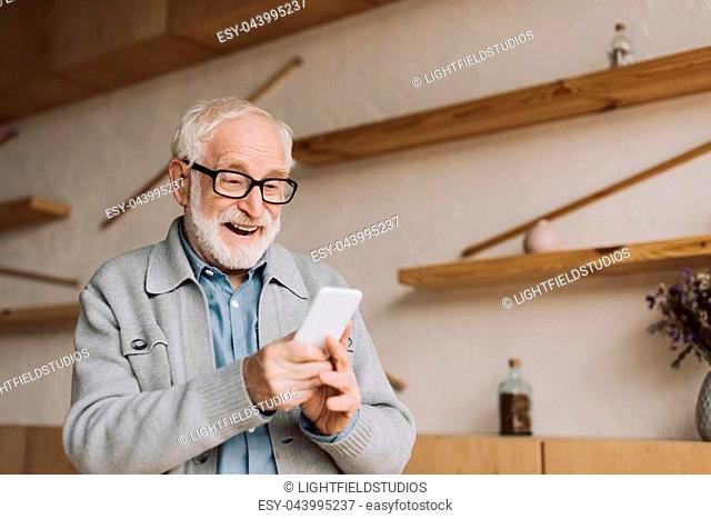 happy senior man using smartphone and looking at camera