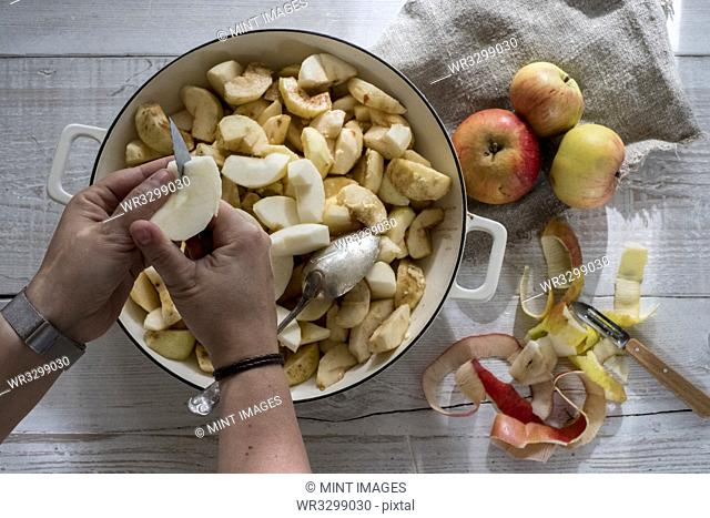 High angle close up of person placing apples in a round baking tin