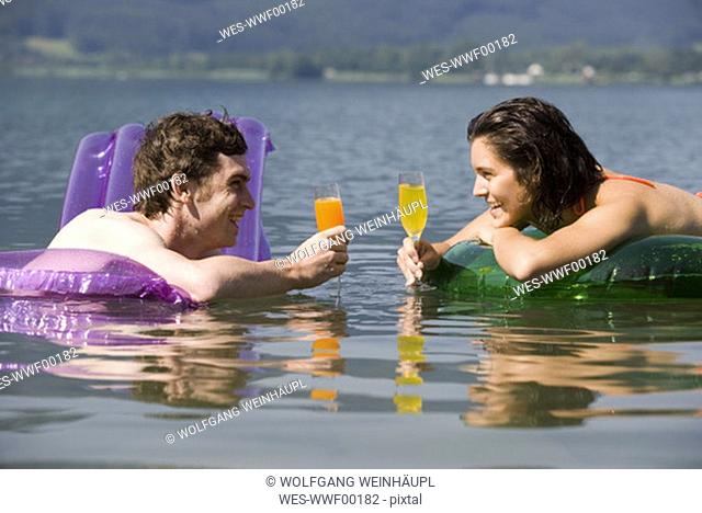 Young couple floating in lake, holding glasses, side view