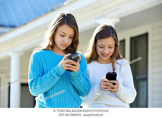 Sister twins having fun with technology mobile smartphone