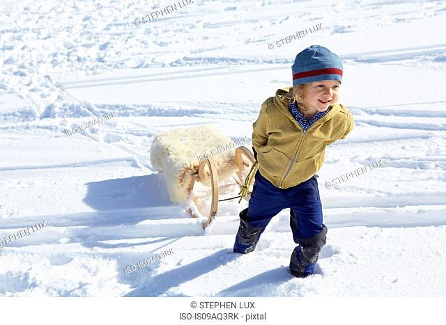 Boy pulling toboggan uphill