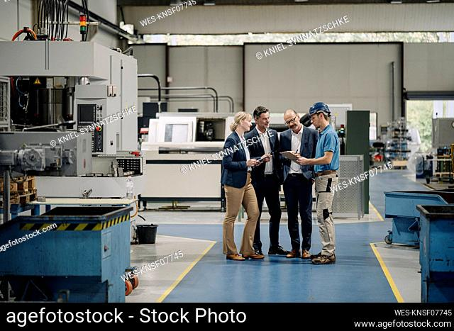Business people and worker talking in a factory