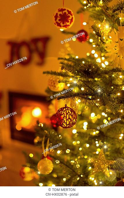Ornaments hanging from Christmas tree with string lights in living room