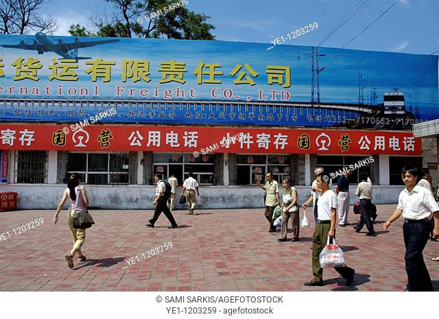 People walking past the ticket sales window at a railway station in Datong, Shanxi, China