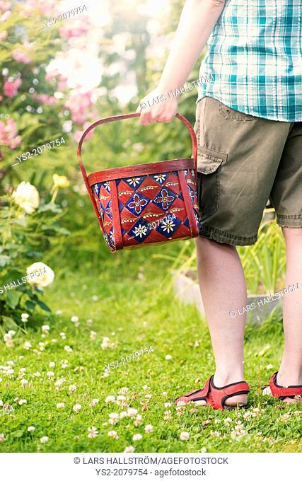 Woman holding basket in vegetable garden, Sweden