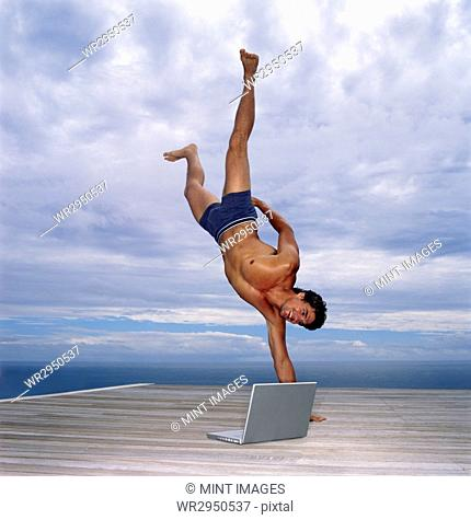 A man in swimming trunks doing a one armed handstand on a deck by the ocean, a laptop by his side