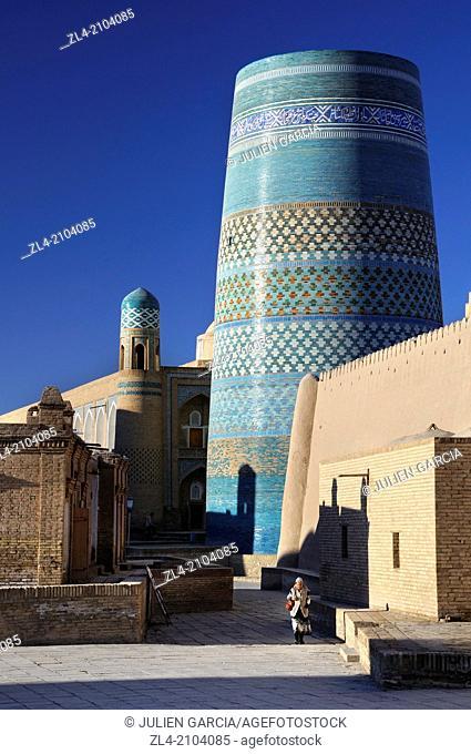 Woman walking by the unfinished minaret Kalta Minor. Uzbekistan, Khorezm, Khiva, Itchan Kala (inner town)