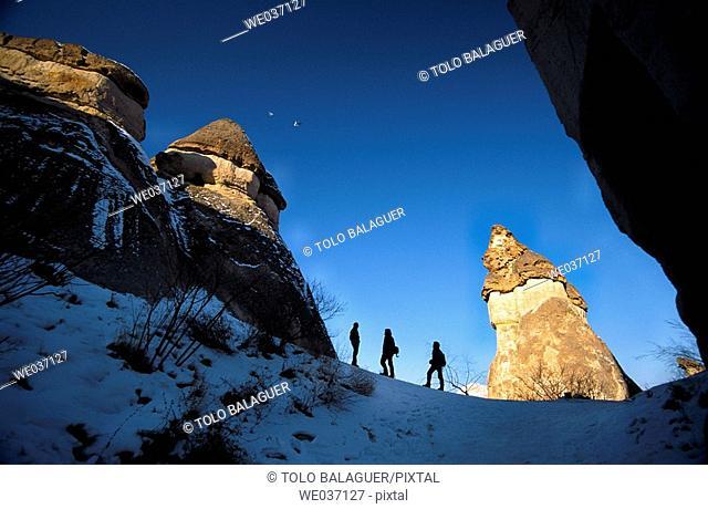 Silhouettes of people between fairy chimneys, Pasabagi, Devrent Valley, Zelve. Cappadocia, Turkey