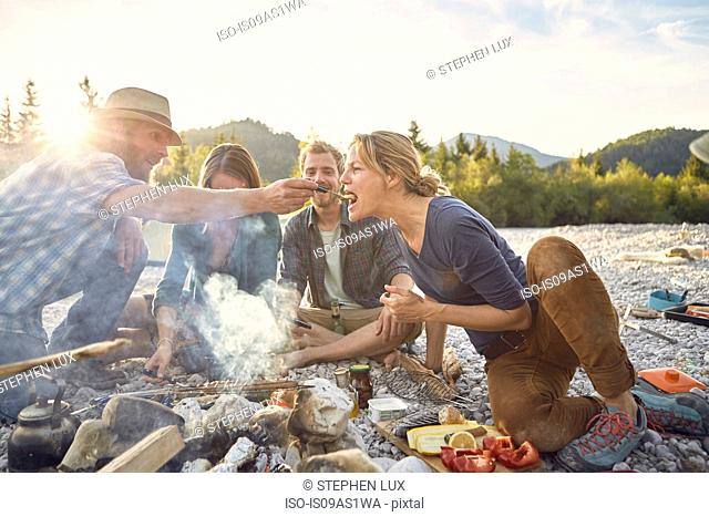 Mid adult man feeding mature woman across a campfire