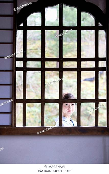 Young Japanese woman in kimono behind window