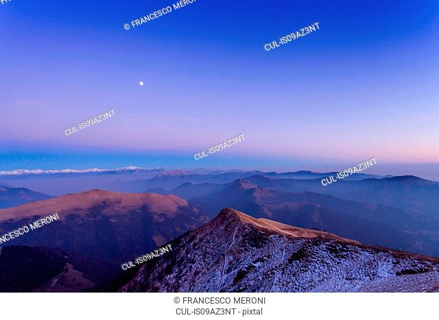 Elevated snow capped mountain landscape with valley mist at dawn, Monte Generoso,Ticino, Switzerland