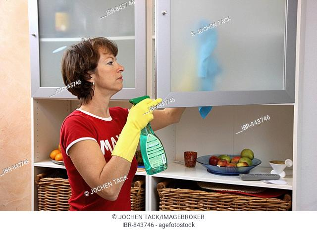 House work, woman cleaning, wiping a cupboard with a damp cloth