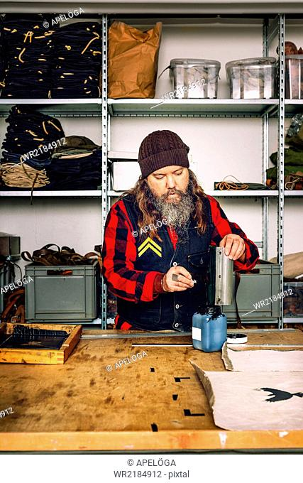 Mature worker filling up remaining ink in bottle from squeegee at worktable