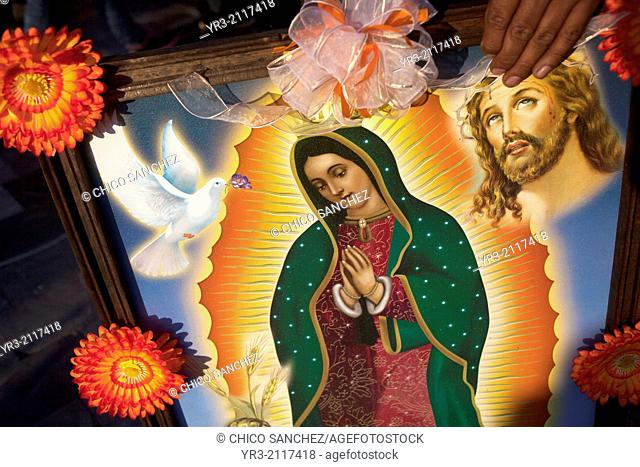 A woman holds a picture of the Virgin of Guadalupe decorated with flowers at the pilgrimage to Our Lady of Guadalupe Basilica in Mexico City, Mexico