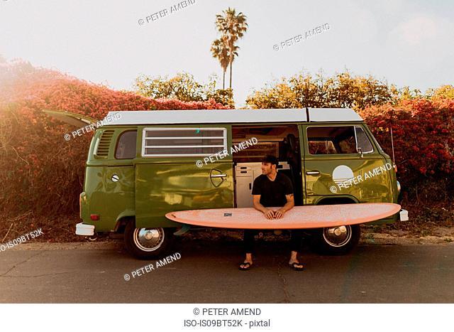Man on van road trip with his surfboard, Ventura, California, US
