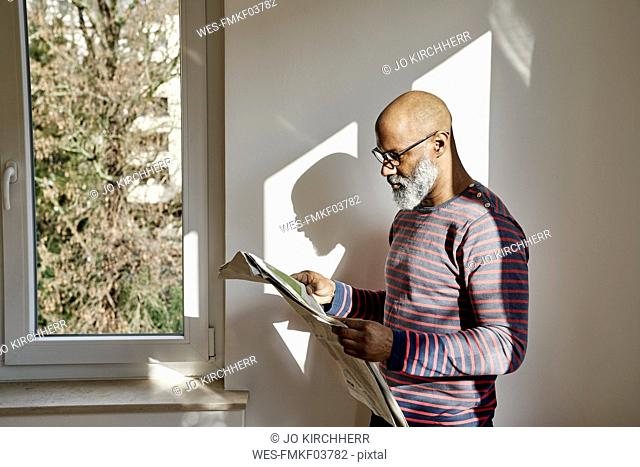Man at the window reading newspaper