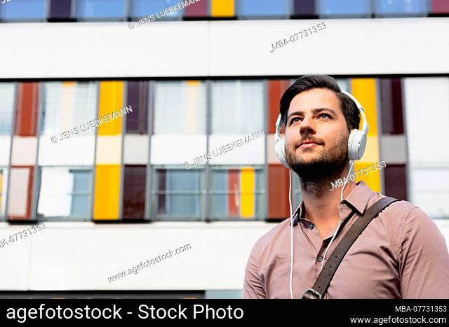 Young man with earphones in front of modern office building, half portrait