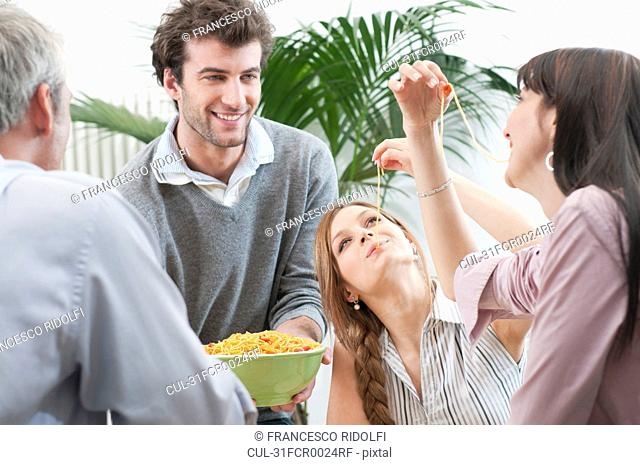 Friends tasting spaghetti for lunch