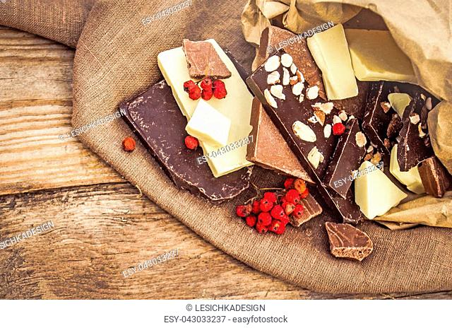 hocolate mix with nuts and dried fruits on rustic wooden background. Chocolate blocks stack with different kind of chocolate. Chocolate bar pieces