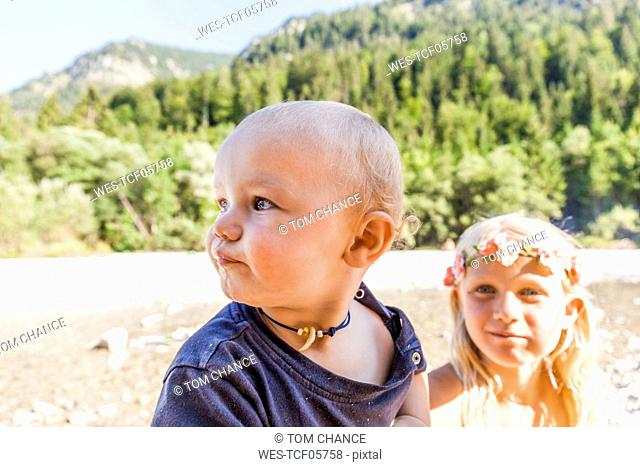 Portrait of baby boy and girl wearing flower crown outdoors in summer
