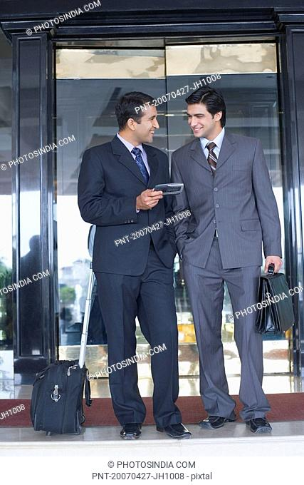 Two businessmen standing in front of a door and smiling
