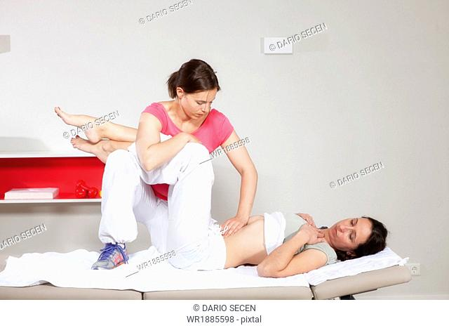 Female patient receiving treatment from osteopath, Munich, Bavaria, Germany