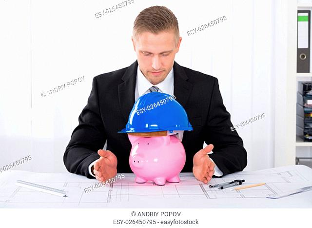 Young Male Architect With Piggybank Wearing Construction Helmet On Blueprint At Desk In Office
