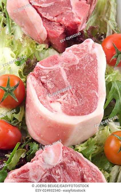 raw lamb chop with tomato and salad on a plate