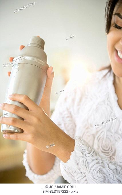 Pacific Islander woman shaking cocktail shaker
