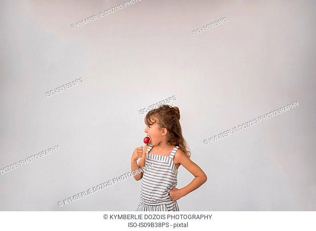 Little girl licking lollipop against white background