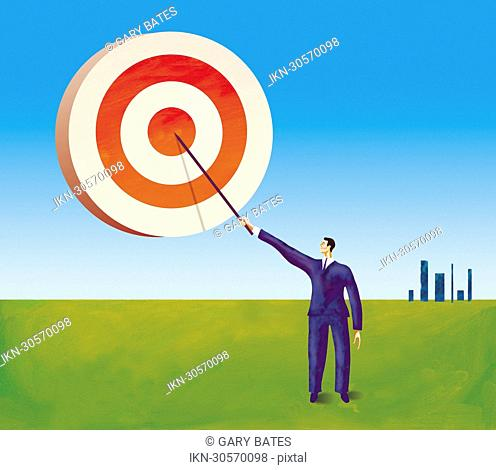 Businessman painting target in the sky