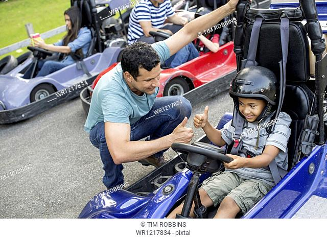 Boys and men go-karting on a track