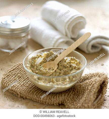 Aloe and elder body scrub in small glass bowl with wooden spoon, close-up
