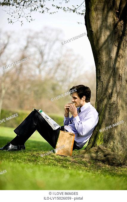 A businessman leaning against a tree, eating a sandwich and reading the newspaper