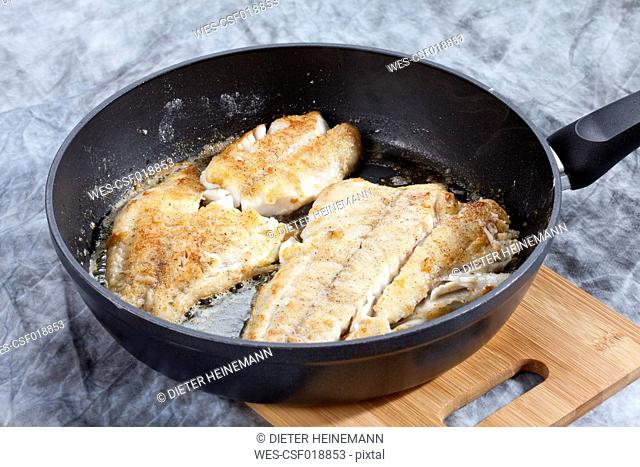Fried pollock fillet in pan, close up