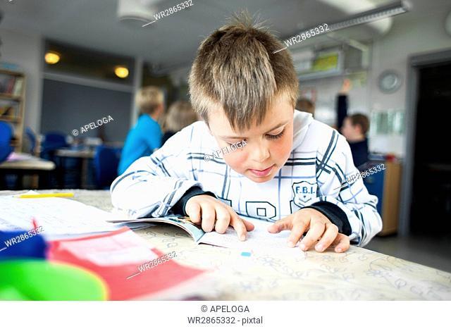 Schoolboy reading book at desk in classroom