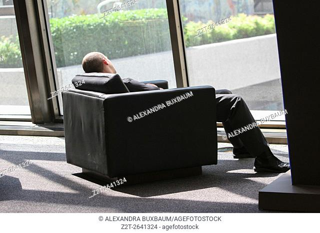 A man rests in a large, comfortable chair