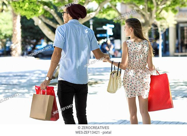 Young couple with shopping bags walking in the city
