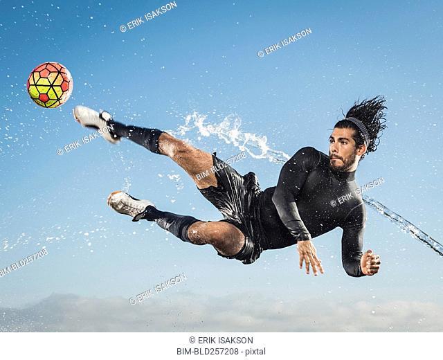Water spraying on Hispanic man kicking soccer ball