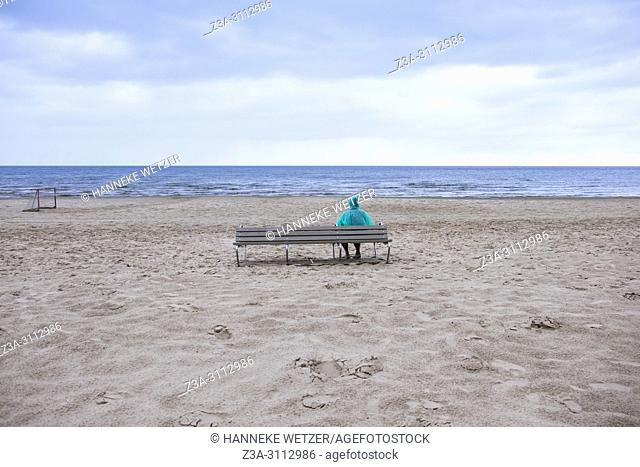Person in a raincoat sitting on a bench, watching the sea