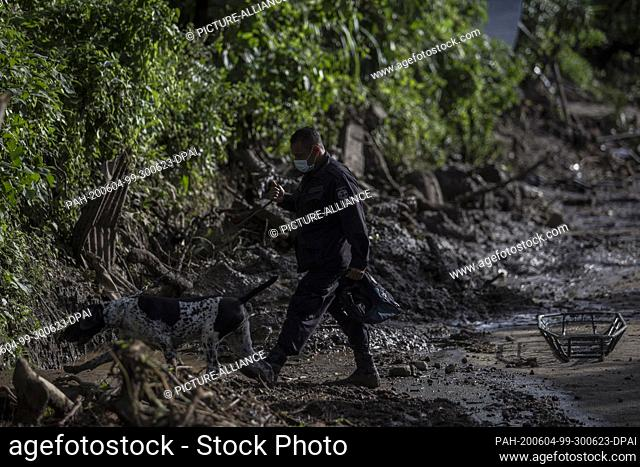 03 June 2020, El Salvador, Santo Tomás: A police officer leads a sniffer dog into an area where people are to be searched for who have been buried in heavy...
