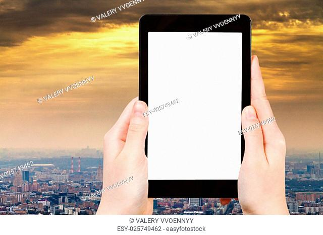 travel concept - hand holds tablet pc with cut out screen and smog over city on background