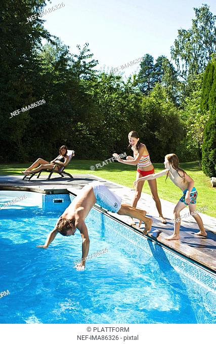 Children pushing father into swimming pool