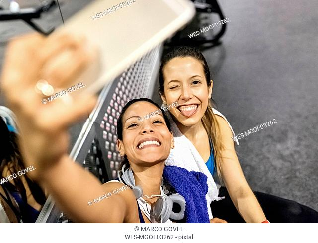 Two women making a selfie after work out in the gym
