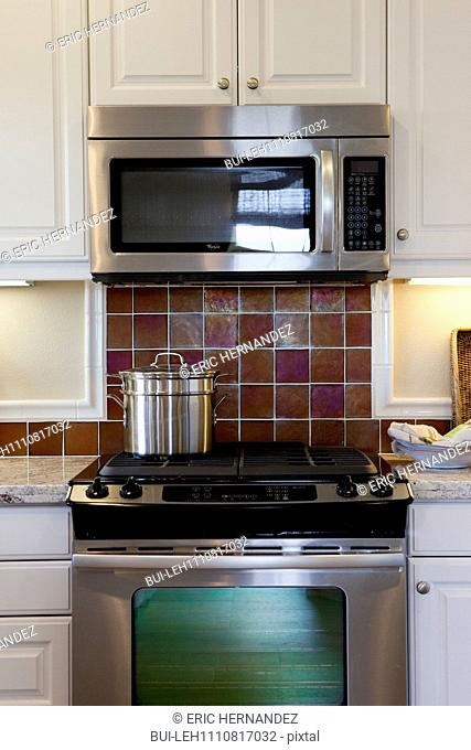 Utensil on stove with oven and white cabinets in kitchen at home