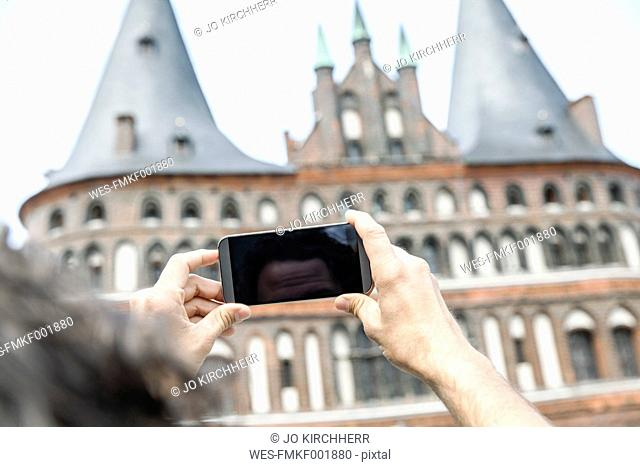 Germany, Luebeck, man taking picture in front of the Holsten Gate
