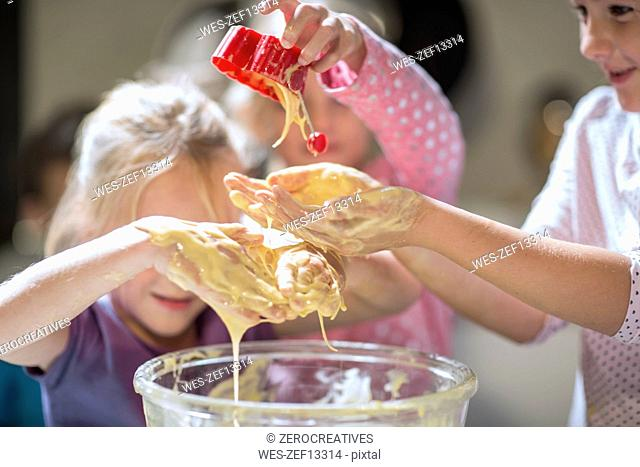 Girls messing with dough in kitchen
