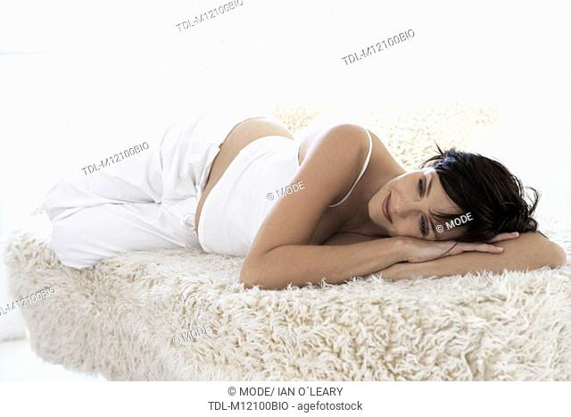 A pregnant woman lying on her side smiling